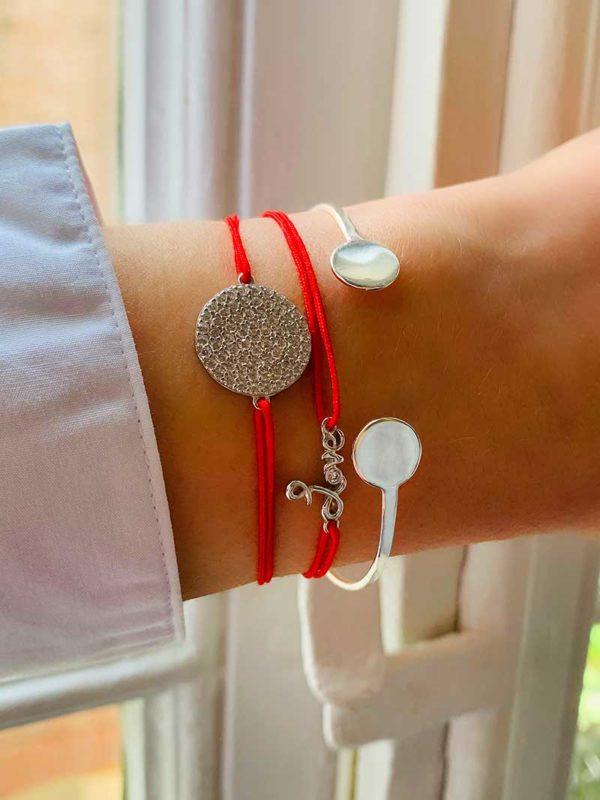 Gros plan poignet devant fenetre avec deux bracelets cordons rouges et pampille en argent et zircons et un bracelet jonc ouvert avec deux plaques rondes
