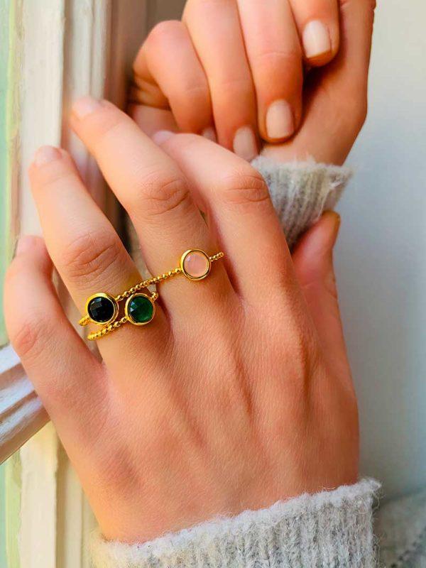 Vue de face gros plan main avec 3 bagues en plaqué or avec pierres semi précieuses