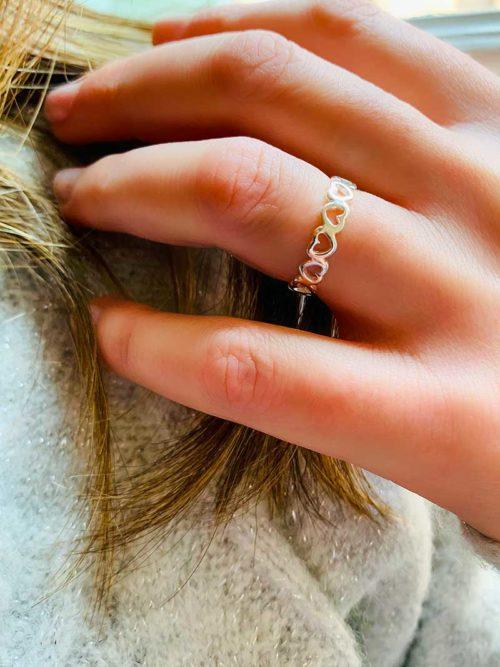 Vue de face gros plan main avec une bague en forme de petits coeurs en argent