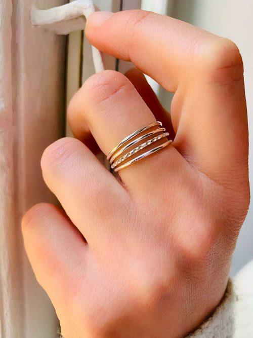 Gros plan main sur fenêtre avec une bague composée de 4 anneaux en argent Bijoux fantaisies