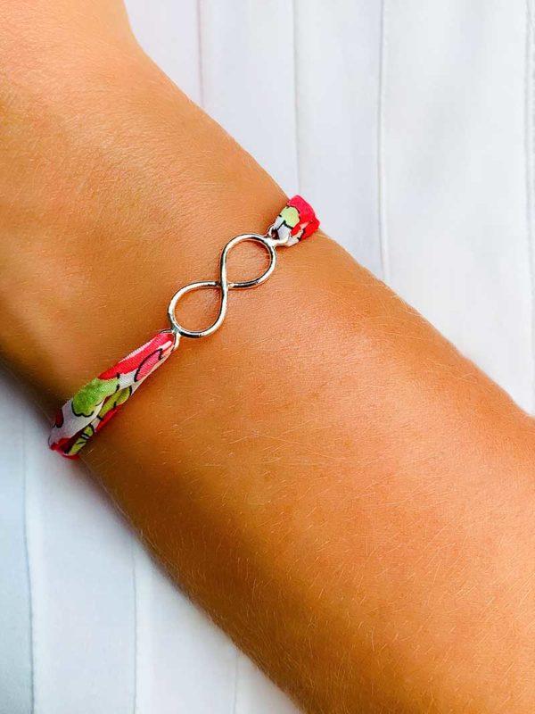 Vue de face gros plan poignet avec bracelet cordon liberty dans les tons de bleu et une breloque en forme d'infini en argent
