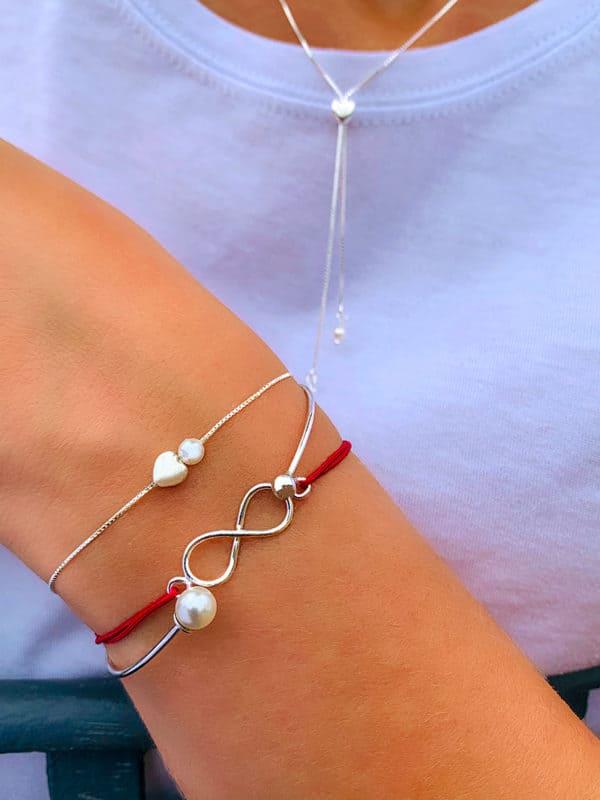 Gros plan bras replié devant buste avec bracelets et collier coeur, perle, symbole infini en argent