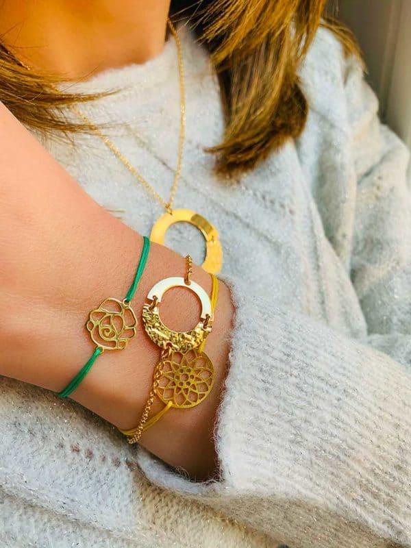 Gros plan haut du buste et bras penché avec bracelets et colliers en plaqué or et bracelets cordons jaune et vert
