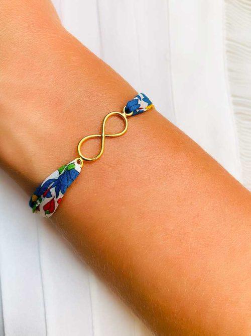 Vue de face gros plan poignet avec bracelet cordon liberty dans les tons de bleu et une breloque en forme d'infini en plaqué or