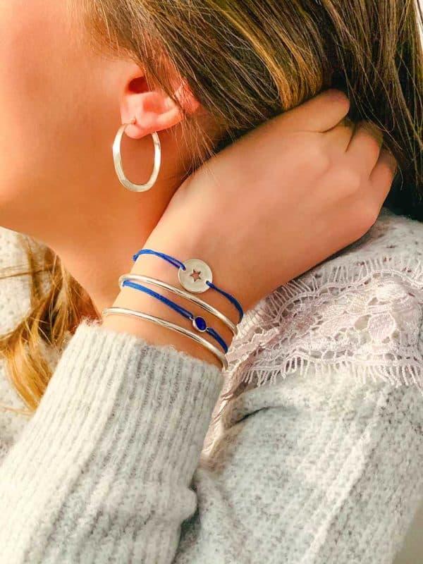 Vue de coté visage et main relevé avec association de boucles d'oreilles anneaux incurvés et bracelets en argent et bracelets cordons bleus