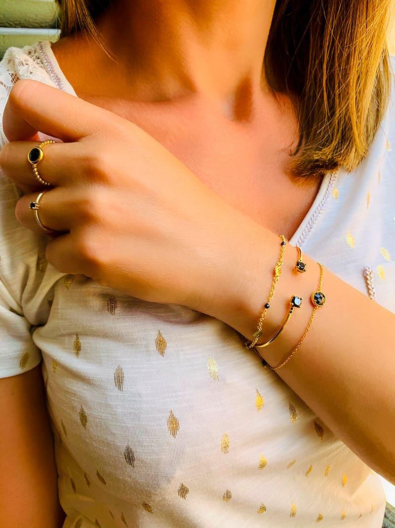 Gros plan bras penché avec bracelets et bagues en plaqué or et pierres semi précieuses en onyx noires