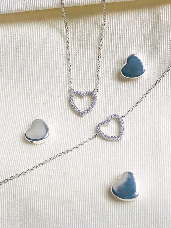 Gros plan bijoux avec des coeurs en argent et zircons posés sur un tissus blanc