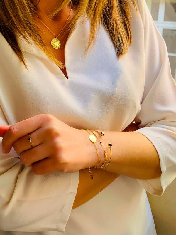 Vue de biais buste et bras croisées avec une association de colliers bracelets et bagues en plaqué or pierres semi précieuses noires et zircons