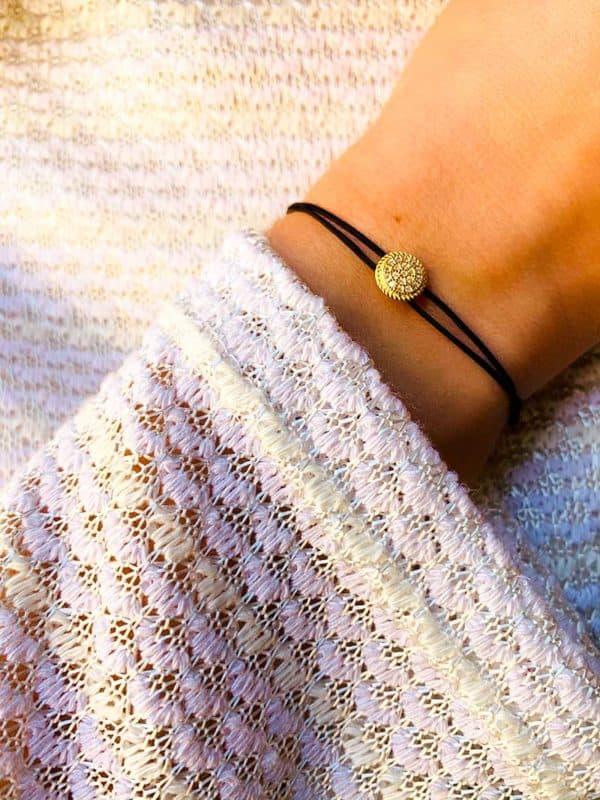 Vue de face poignet avec bracelet cordon noir et pampille en forme de plaque en plaqué or inscrustée de zircons