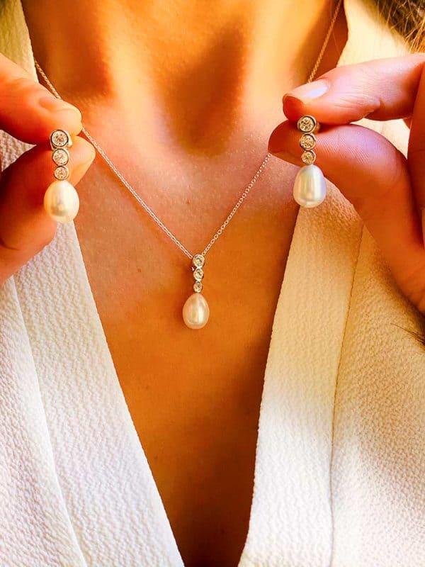 Vue de face parure collier et boucles d'oreilles en argent avec pendentif en zircons et perle