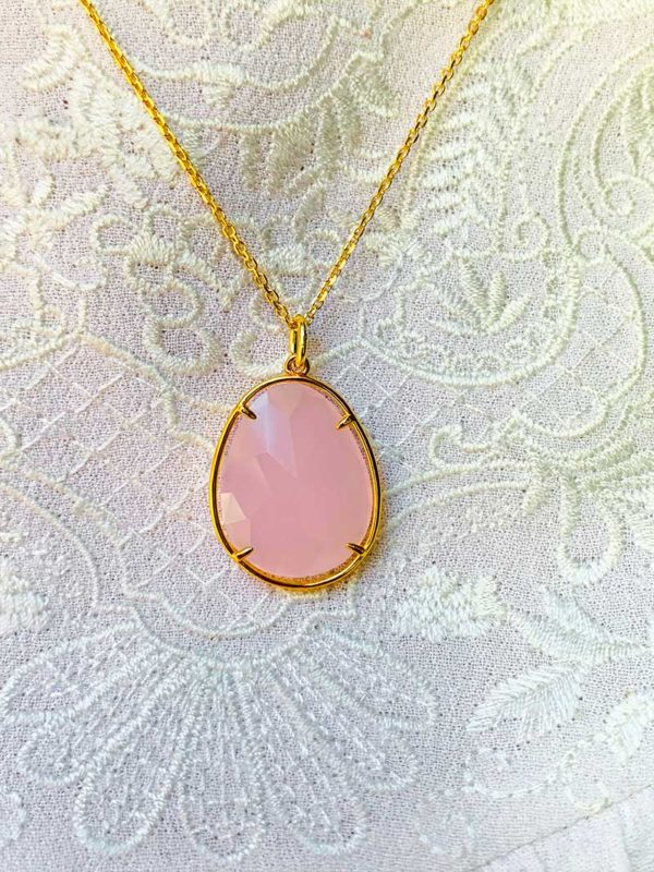 Vue de face gros plan collier en plaqué or avec une grosse pierre semi précieuse ovale en quartz rose