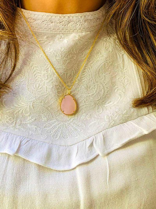 Vue de face gros plan buste avec collier en plaqué or avec une grosse pierre semi précieuse ovale en quartz rose