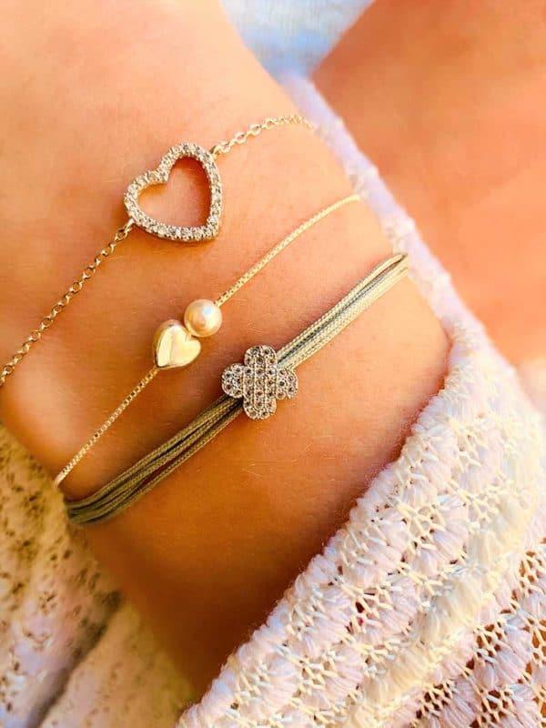 Gros plan poignet penché avec une association de bracelet en argent avec perle et zircons