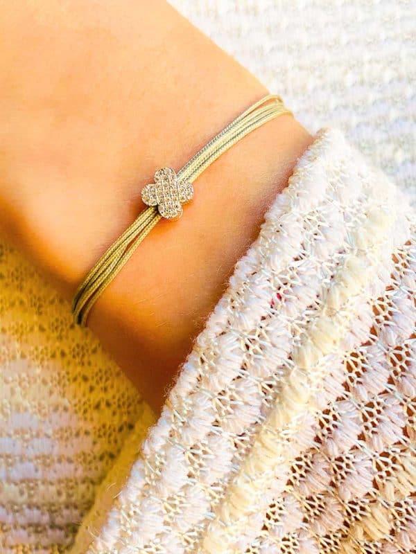 Vue de face gros plan poignet avec bracelet cordon gris avec fleur coulissante en argent et zircons blancs . Bracelet réglable et choix de couleur de cordon