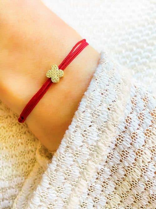Vue de face gros plan poignet incliné avec bracelet cordon prune avec fleur coulissante en plaqué or et zircons blancs . Bracelet réglable et choix de couleur de cordon