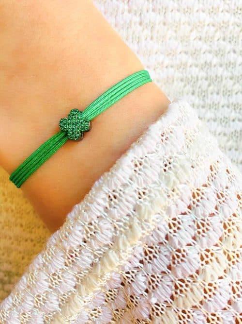 Vue de face gros plan poignet avec bracelet cordon vert avec fleur coulissante en ruthénium noir et zircons verts. Bracelet réglable et choix de couleur de cordon