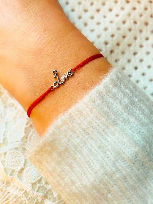 Vue de face gros plan poignet avec bracelet cordon et un love manuscrit en argent avec un zircon. Bracelet réglable et choix de couleur de cordon