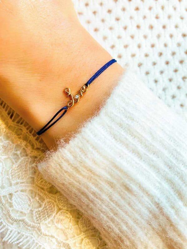 Vue de face gros plan poignet avec bracelet cordon et un love manuscrit en plaqué or avec un zircon. Bracelet réglable et choix de couleur de cordon