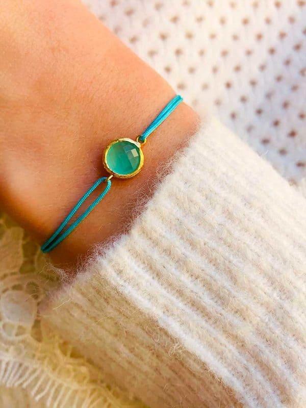 Vue de face gros plan poignet avec bracelet cordon pierre semi précieuse de calcédoine et plaqué or. Eshop bijoux fantaisies