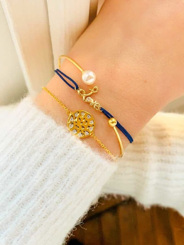Vue de face gros plan poignet avec bracelet cordon et un love manuscrit en plaqué or avec un zircon, et les bracelets Olivia un jonc ouvert avec perle en plaqué or et Elsa une plaque incrusté de zircons en plaqué or