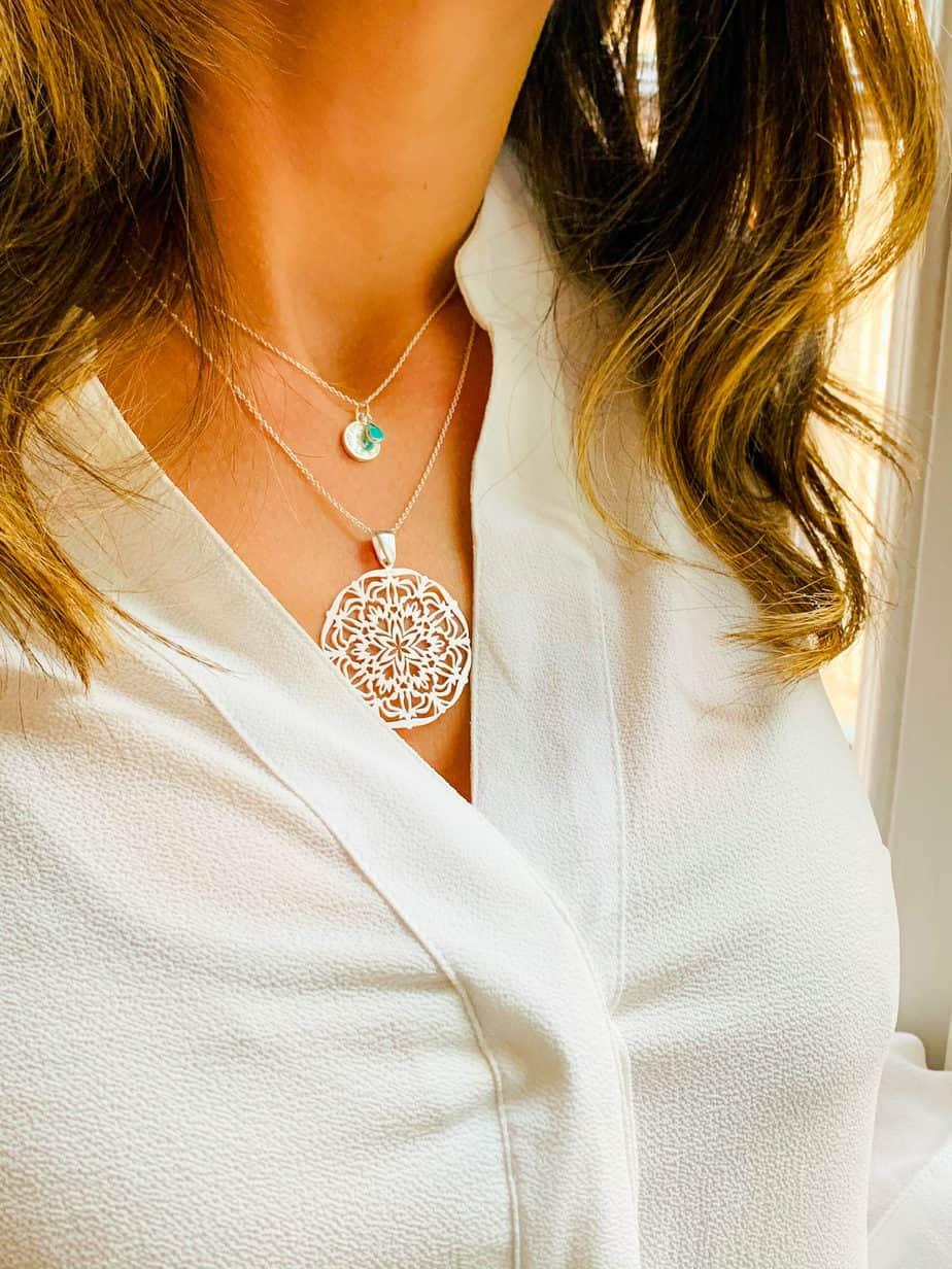 Vue 3/4 avant d'une femme en chemisier blanc portant 2 colliers en argent
