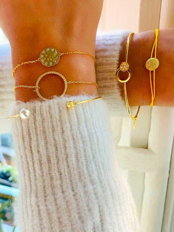 Gros plan Poignets croisés avec des bracelets en plaqué or et zircons