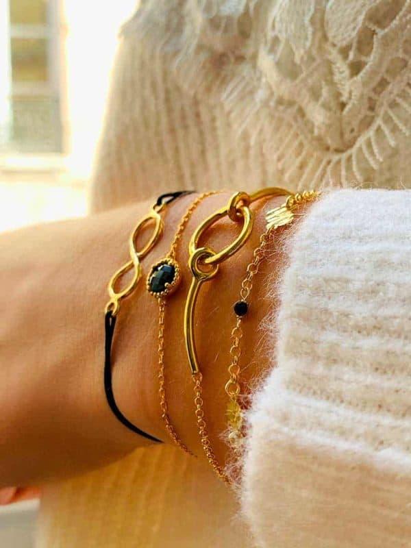 vue 3/4 collections bracelets plaqué or avec pierre noire onyx avec une vue sur fenètre en arrière plan