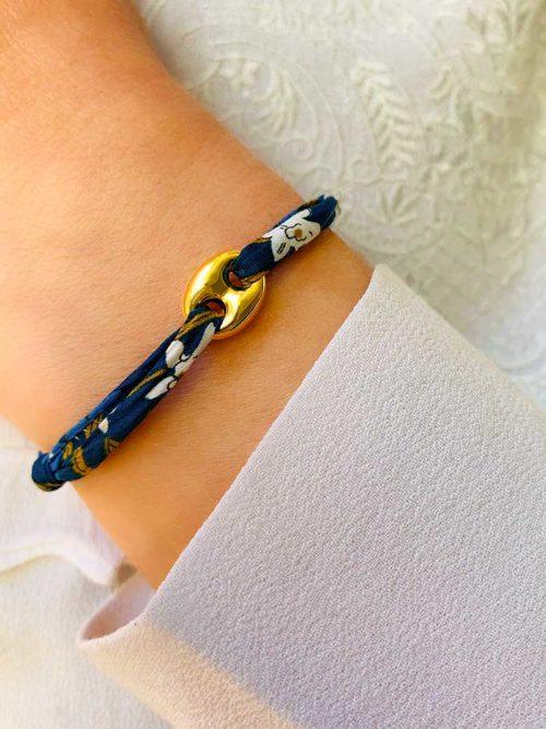 Vue de face gros plan poignet bracelet cordon liberty bleu avec pampille maille marine en plaqué or