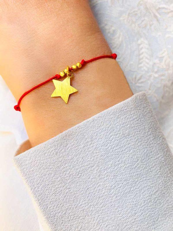 Vue de face gros plan poignet penché avec bracelet cordon céline doré en plaqué or avec 4 petites perles et une étoile pendante