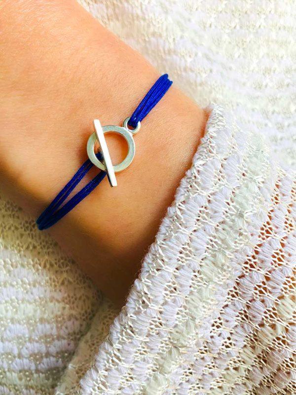 Gros plan poignet avec bracelet cordon bleu et fermoir à attache en argent