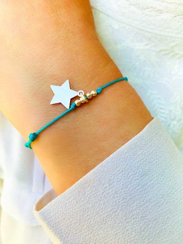 Vue de face gros plan poignet avec bracelet cordon bleu ciel avec un charm en forme d'étoile en argent mat et 4 petites perles en argent