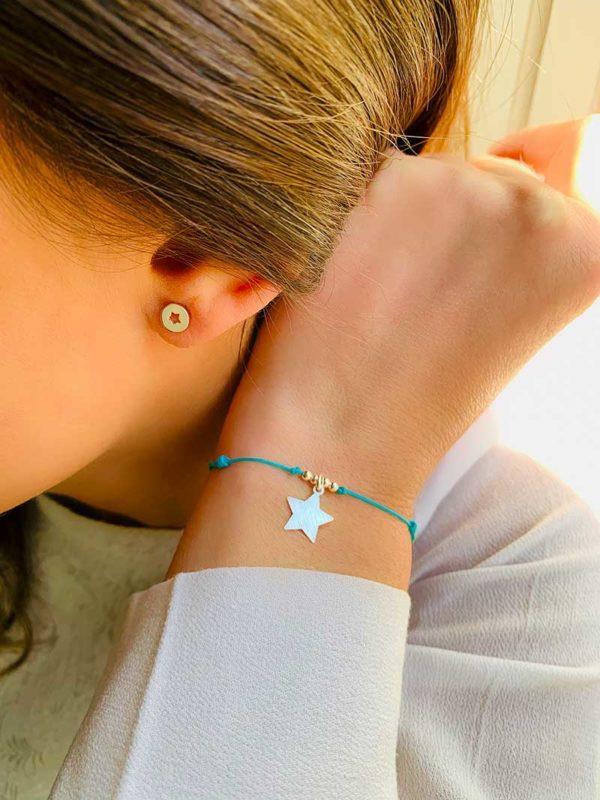 Gros plan de profil oreille avec boucle d'oreille en argent avec une étoile ajourée et bracelet cordon avec un charm en étoile et 4 petites perles en argent