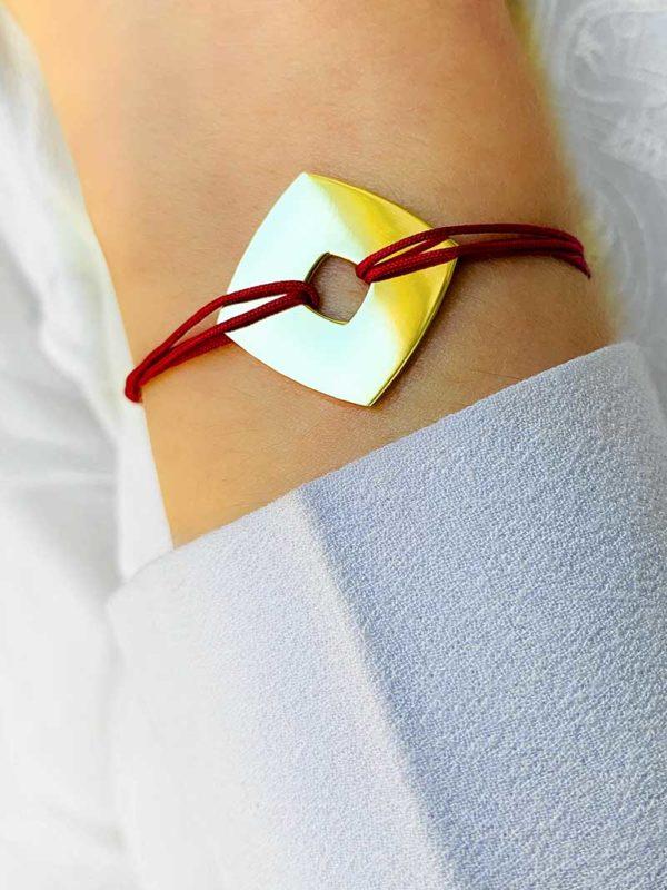 Vue de face gros plan poignet avec bracelet cordon rouge avec une plaque carré ajourée en plaqué or