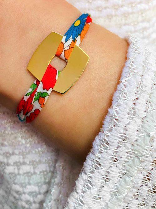 Vue de face gros plan poignet avec bracelet cordon en liberty avec une plaque carrée en plaqué or