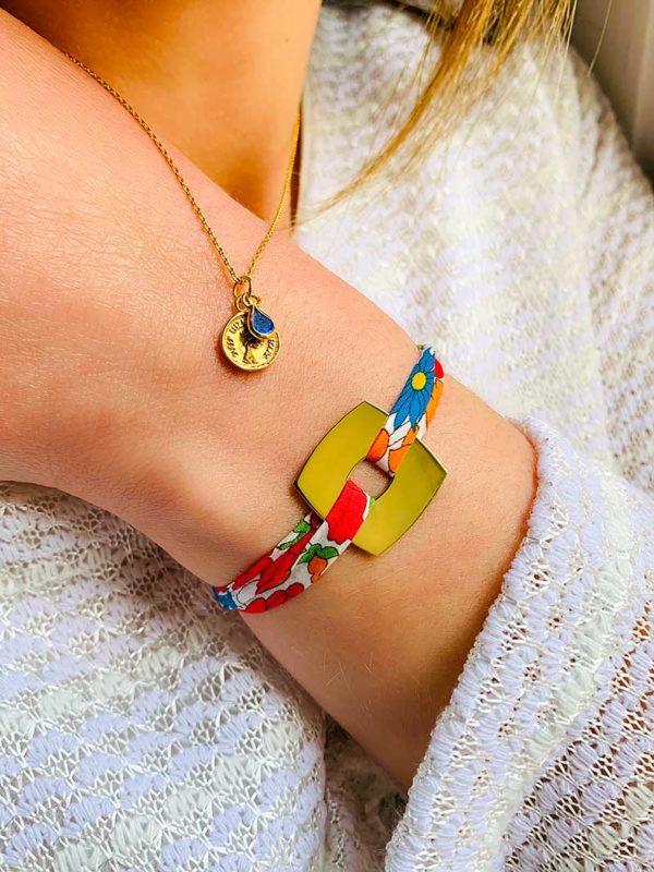 Gros plan buste avec bras plié et porté un collier en plaqué or avec pièce de monnaie et une pierre lapis lazulli et un bracelet cordon liberty avec une plaque carrée en plaqué or