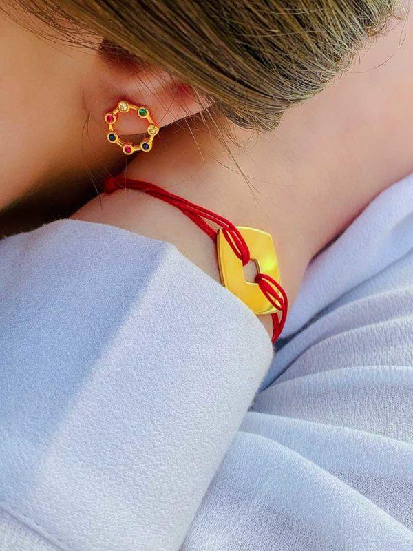 Gros plan oreille avec boucles d'oreilles en plaqué or et zircons multicolores avec bras replié, au poignet un bracelet cordon rouge avec une plaque carré ajourée en plaqué or