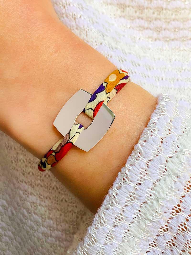Vue de face gros plan poignet avec bracelet cordon en liberty avec une plaque carrée en argent