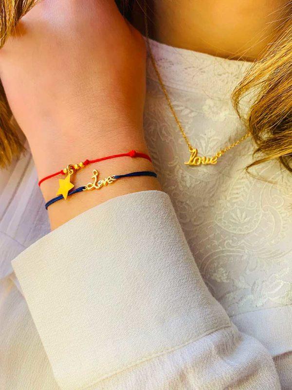 Vue de face buste avec collier en plaqué or avec un love manuscrit, et un poignet penché avec deux bracelet cordon un love manuscrit avec zircon et une étoile pendante entourée de petites perles tout en plaqué or