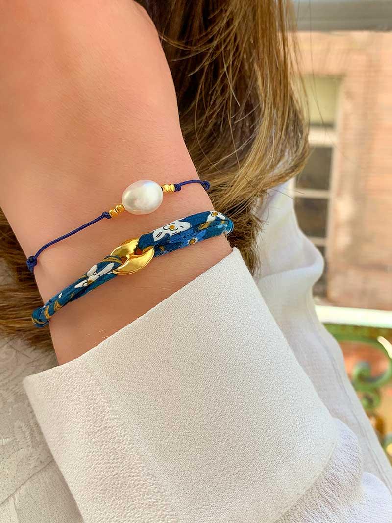 Vue de face gros plan poignet avec deux bracelets cordons, l'un en liberty bleu et maille marine en plaqué or et l'autre un cordon bleu avec une perle baroque et 4 petites perles en plaqué or