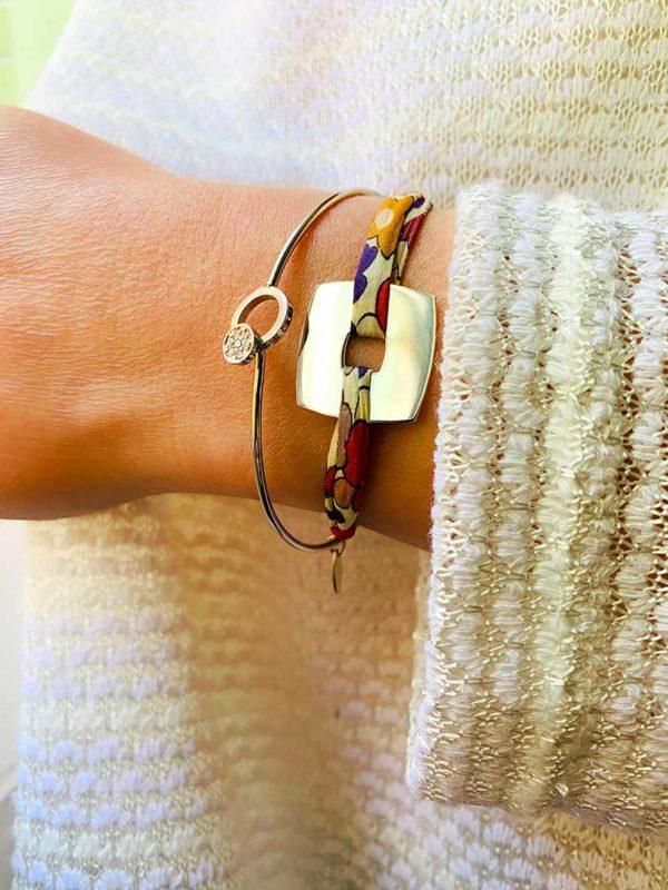 Vue de face gros plan poignet avec bracelet cordon en liberty avec une plaque carrée en argent et bracelet jonc en argent avec cercle en zircon