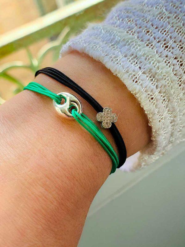 Gros plan poignet devant fenetre avec Bracelets cordons en argent et zircons avec une maille marine et un avec une fleur coulissante