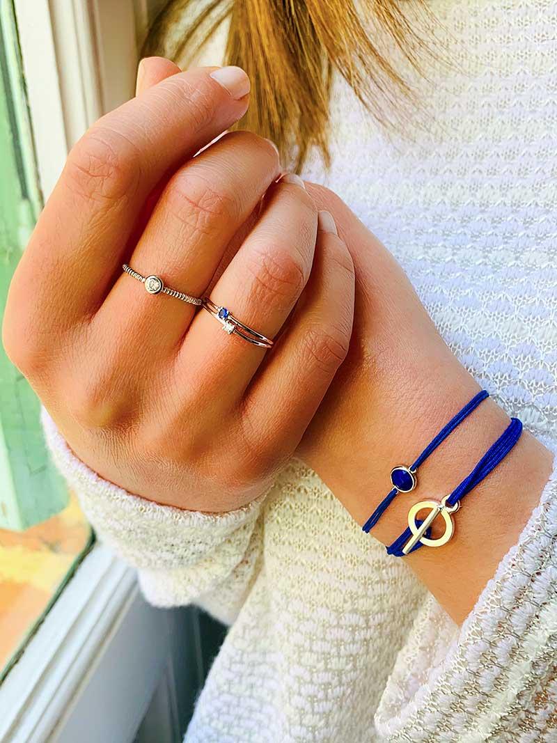 Gros plan 2 mains l'une dans l'autre devant une fenêtre, avec assortissement de bagues et bracelets cordons en argent et pierres bleues