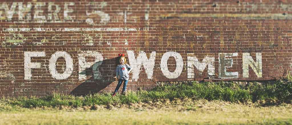 petite fille blonde devant un mur de briques