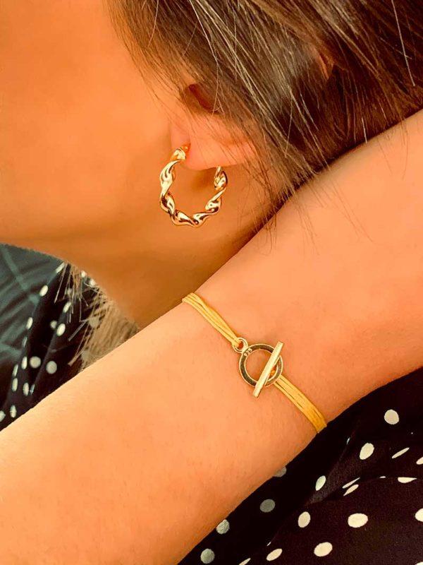 Vue de profil gros plan bras relevé et bas du visage avec un bracelet cordon au poignet et une boucle d'oreille style créole torsadé. Bijoux en plaqué or