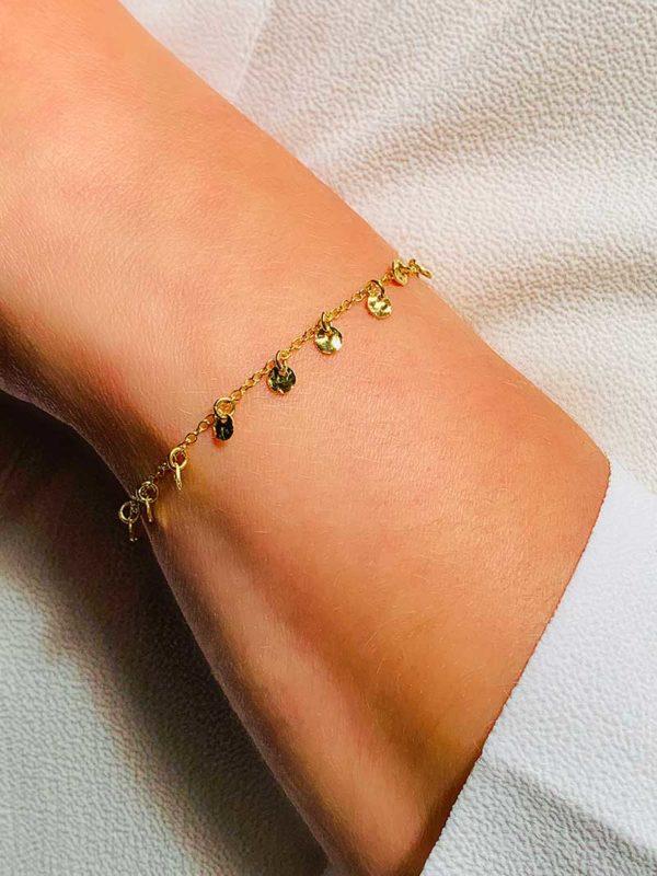 Vue de face gros plan poignet avec un bracelet en plaqué or 925/1000. Une fine chaîne avec des pampille en forme de petites plaques rondes avec un effet martelé