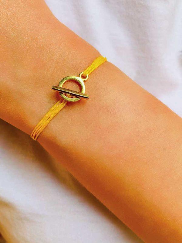 Vue de face gros plan poignet avec bracelet cordon avec une attache avec une barre dans un cercle en plaqué or