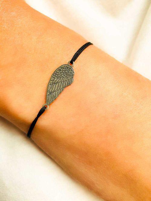 Vue de face gros plan poignet penché avec un bracelet cordon avec une aile ciselée en argent bijoux fantaisies