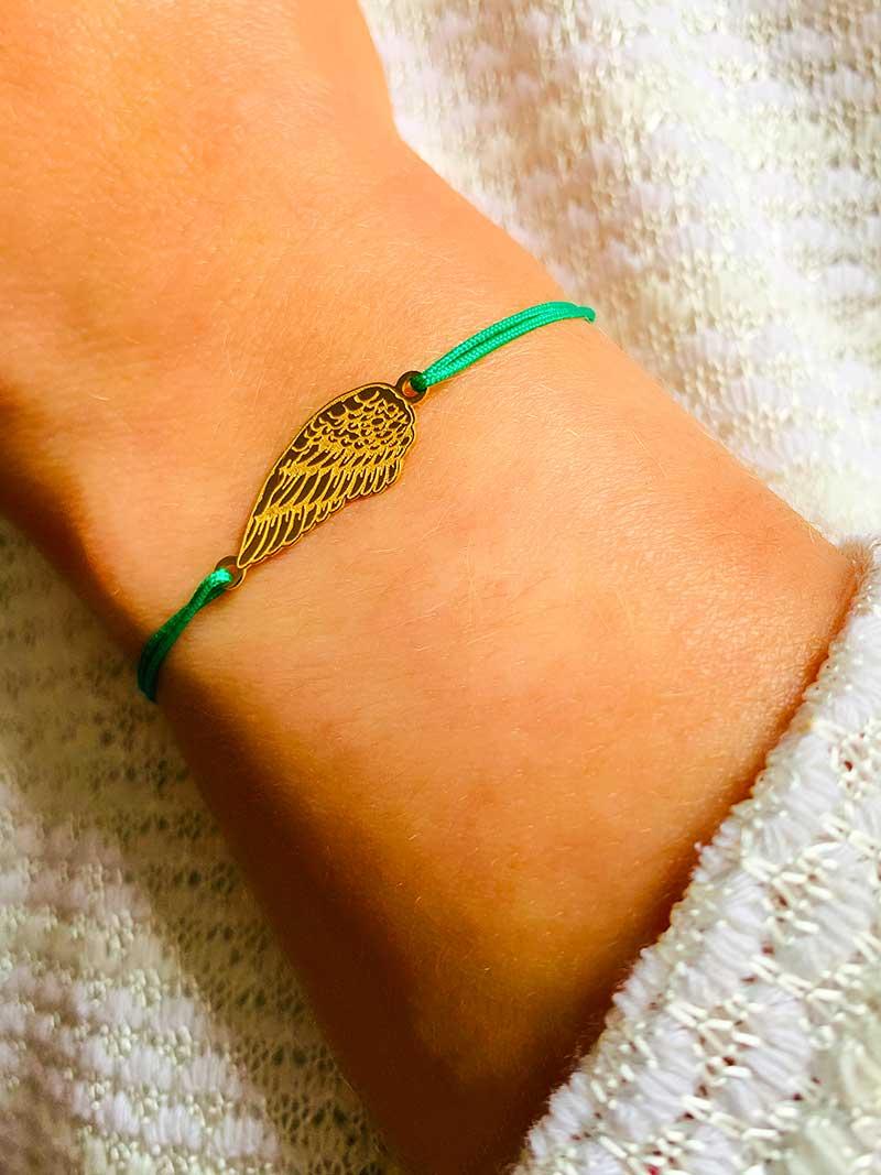 Vue de face gros plan poignet penché avec un bracelet cordon avec une aile ciselée en plaqué or bijoux fantaisies