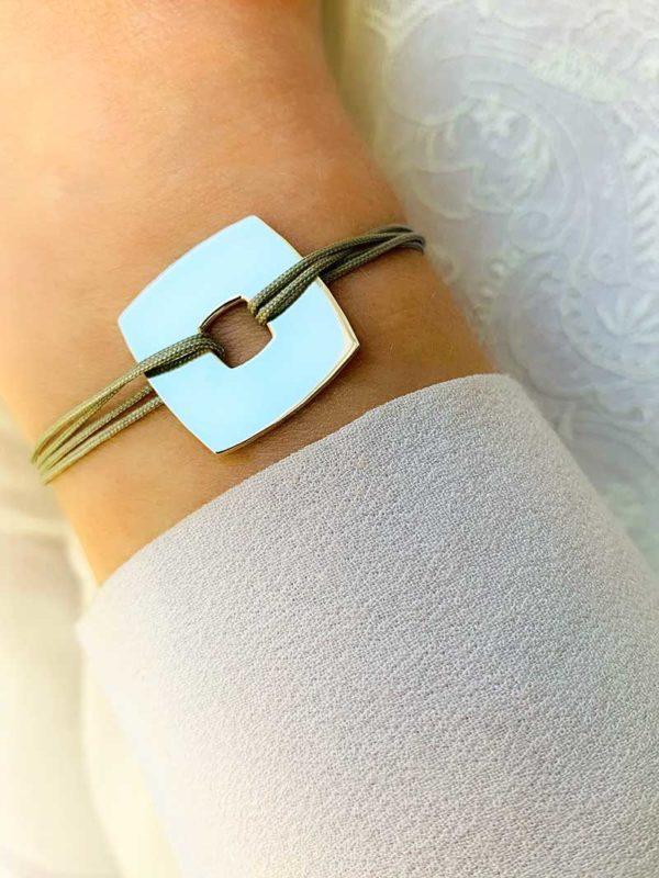 Vue de face gros plan poignet avec bracelet cordon avec une plaque carrée en argent