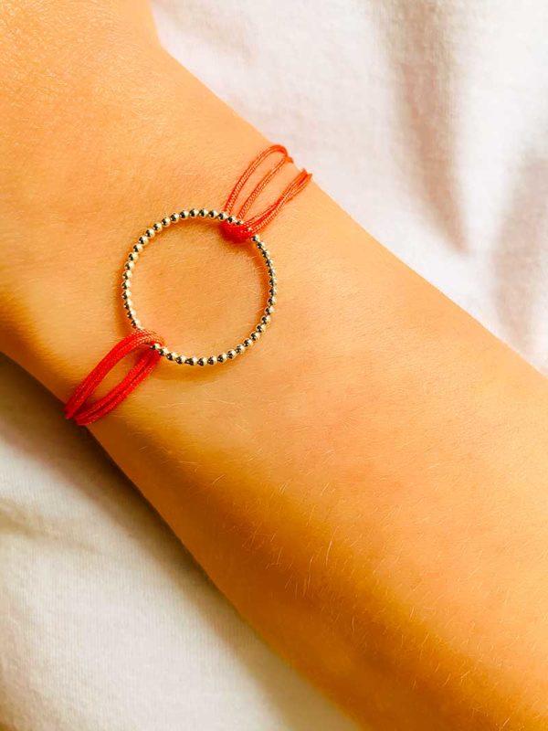 Gros plan vue de face un poignet penché avec un bracelet cordon avec imprimé et un cercle ajouré de petites boules en argent 925